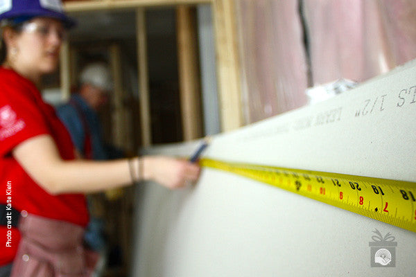 A woman measures drywall as part of construction training; Photo credit: Katie Klein