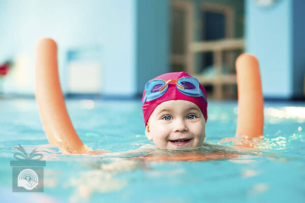 A young girl smiles while learning to swim in a pool with a foam noodle