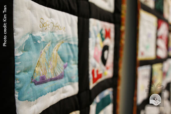 "A quilt with a patch reading ""Safe House"" hangs on a wall; Photo credit: Kim Tran"