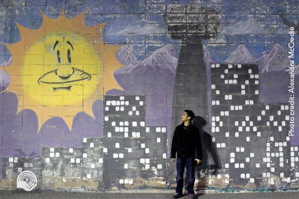 A young man stares at a mural of a smiling sun. Photo credit: Alexandra McCredie