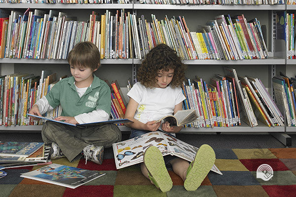Two children sit surrounded by books