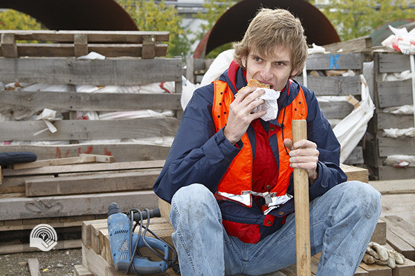 A man eats lunch while holding his sledge hammer