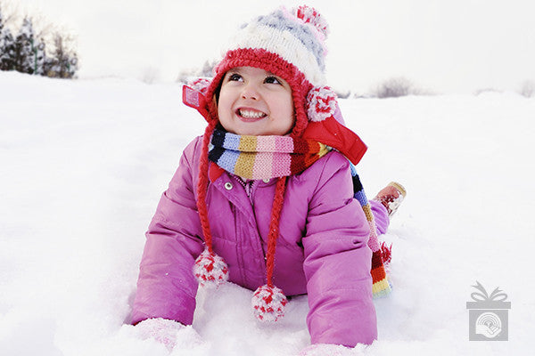 A little girl plays in the snow in her pink snow suit and winter boots