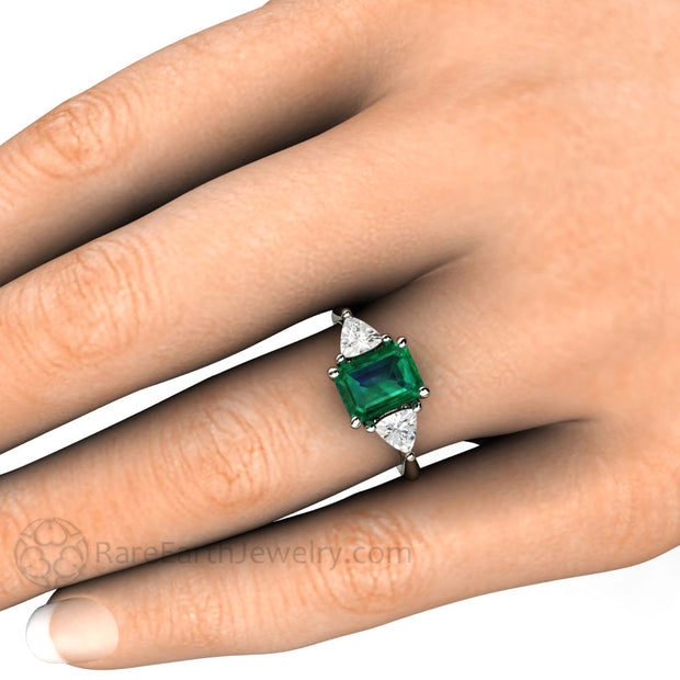 Emerald Ring on the Finger Emerald Cut 3 Stone Setting by Rare Earth Jewelry