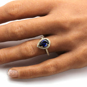 Large Pear Cut Blue Sapphire Diamond Halo Engagement ring on the Finger