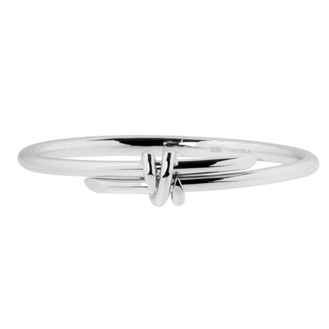Sterling silver wrap bangle with two bands that cross at the front. They have tapered ends and bangle is hinged for easy wrist placement, ref 7387.
