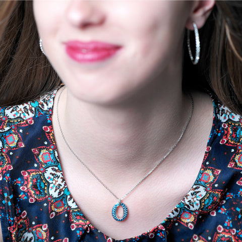 Oxford pendant is an oval, sterling silver cut-out pendant decorated with synthetic blue sapphires on a fine sterling silver chain, pendant 22mm long, ref 7455.