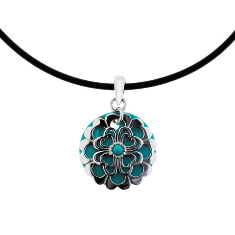 Finely crafted sterling silver stencil pendant, featuring double-heart shapes, layered over reconstituted turquoise. The pendant is hung on a black neoprene choker, ref 7530.