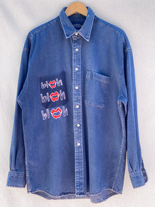 FRONT IMAGE OF BUTTON DOWN DENIM SHIRT WITH BLAH BLAH BLAH EMBROIDERED ON FRONT RIGHT CORNER POCKET.
