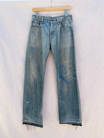 FRONT IMAGE OF FADED BLUE JEANS WITH ROLLED OUT HEM. PUNK ROCK EMBROIDERY AT TOP LEFT POCKET. LITTLE HOLES ARE VISIBLE THROUGHOUT THE FRONT.