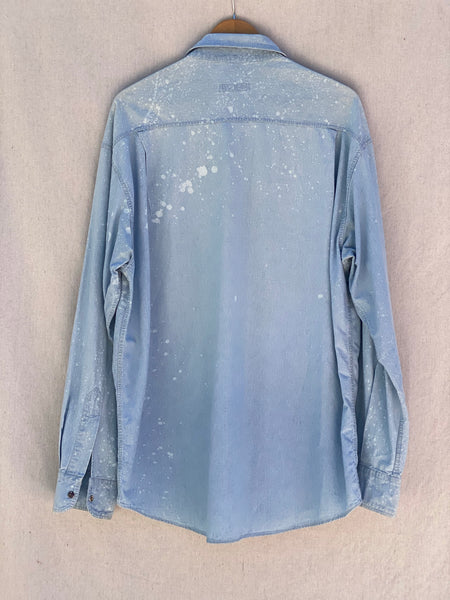 BACK IMAGE OF OVERSIZED DENIM BUTTON DOWN WITH PAINT SPLATTER IN WHITE.