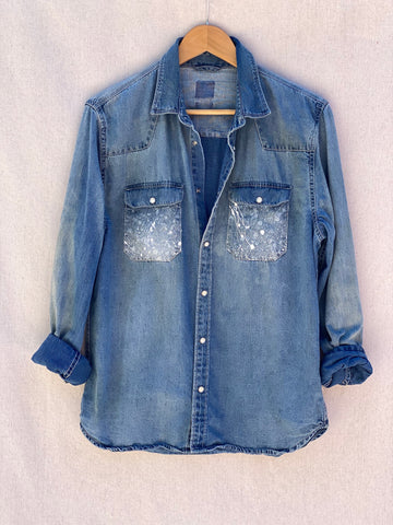 FRONT IMAGE OF DENIM BUTTON DOWN SHIRT WITH PAINT SPLATTERS ON FRONT POCKETS.
