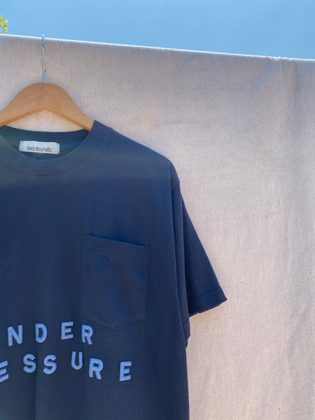 CLOSE UP OF FRONT T-SHIRT, TOP LEFT CORNER, NECK AND SLEEVE. PARTIAL EMBROIDERY SHOWING.