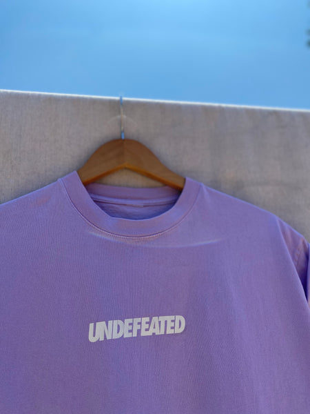 CLOSE UP VIEW OF FRONT NECK AND UPPER CHEST WITH UNDEFEATED PRINT IN WHITE