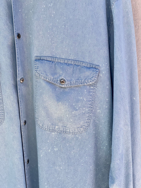 CLOSE UP IMAGE OF LEFT FRONT POCKET WITH WHITE PAINT SPLATTER AND SNAP BUTTONS.
