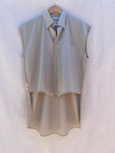 FRONT VIEW OF SLEEVELESS, HI-LO BUTTON DOWN SHIRT IN TAUPE. FRONT SHIRT IS VISIBLY SHORTER THAN BACK.