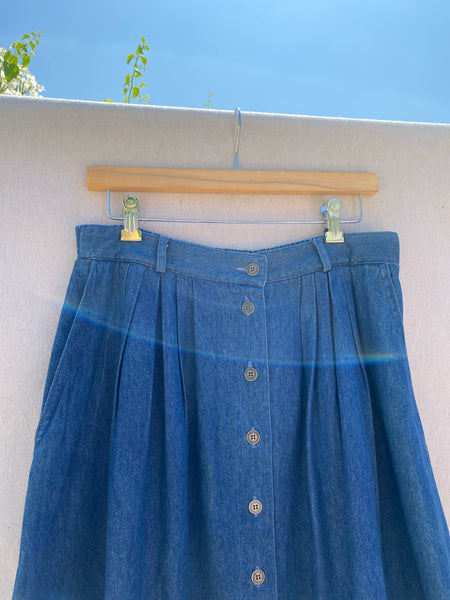 CLOSE UP VIEW OF SKIRT  TOP WAIST, SIDE POCKETS, PLEATS AND CENTER FRONT BUTTONS.