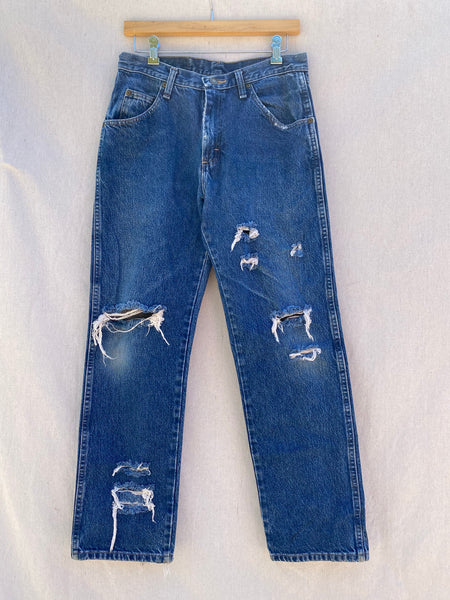 FRONT IMAGE OF VINTAGE RIPPED AND FRAYED BLUE JEANS.