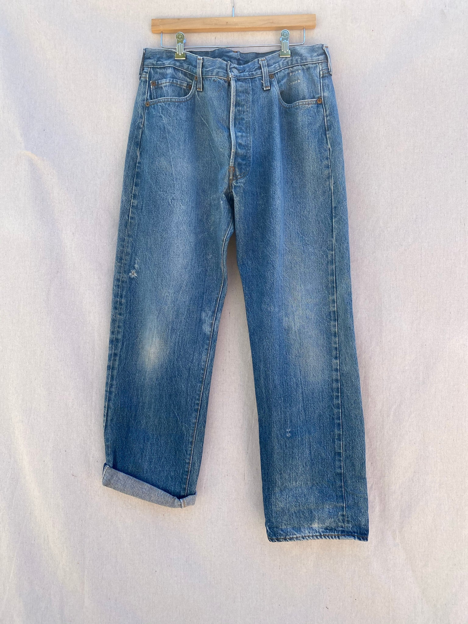 FRONT IMAGE OF FADED BLUE JEANS WITH SMALL PUNK ROCK EMBROIDERY AT TOP LEFT POCKET. RIGHT LEG HEM IS CUFFED/ FOLDED.