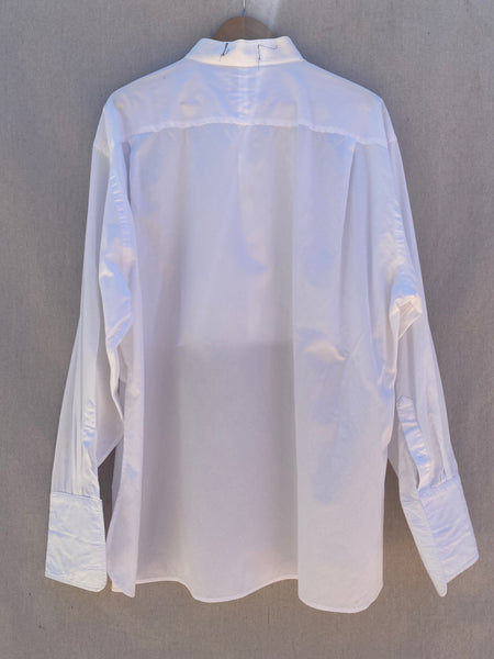 BACK VIEW OF WHITE LONG SLEEVE BUTTON DOWN SHIRT.