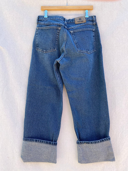 BACK VIEW OF WRANGLER BLUE JEANS WITH FOLDED CUFFS.