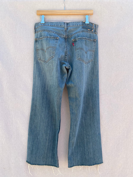 BACK IMAGE OF BLUE JEANS WITH FRAYED RAW HEM.