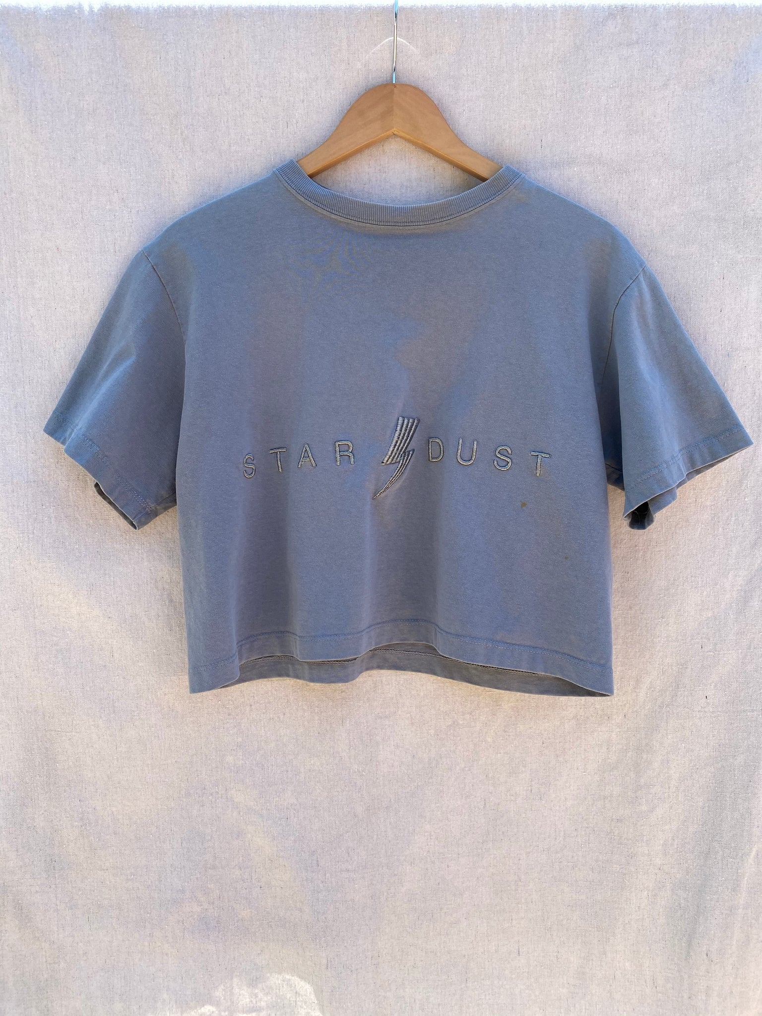 FULL FRONT VIEW OF CROPPED TEE IN SLATE GREY WITH STAR DUST EMBROIDERY ON IT.