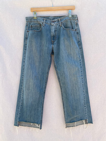 FRONT IMAGE OF FADED LEVI'S JEANS WITH CROPPED AND FRAYED HEM.