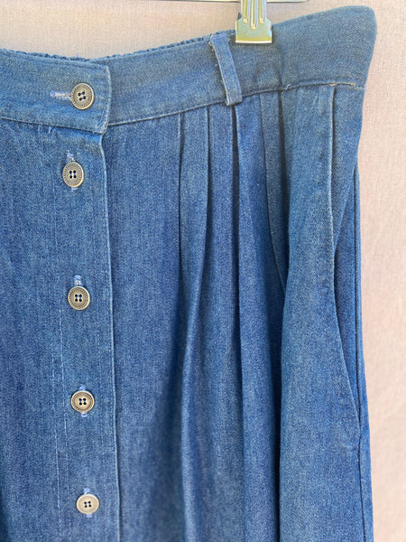 CLOSE UP IMAGE OF FRONT BUTTONS,  PLEATS AND SIDE POCKET.