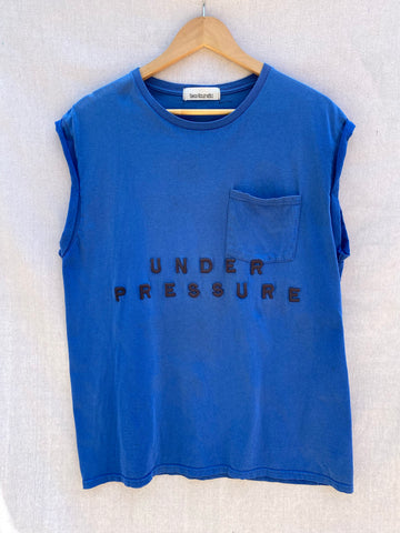 FRONT VIEW OF BLUE MUSCLE TEE WITH UNDER PRESSURE EMBROIDERY IN BLACK. ALSO INCLUDES POCKET AT TOP LEFT CORNER.