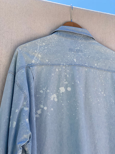 CLOSE UP IMAGE OF BACK SHOULDER YOKE WITH WHITE PAINT SPLATTER.