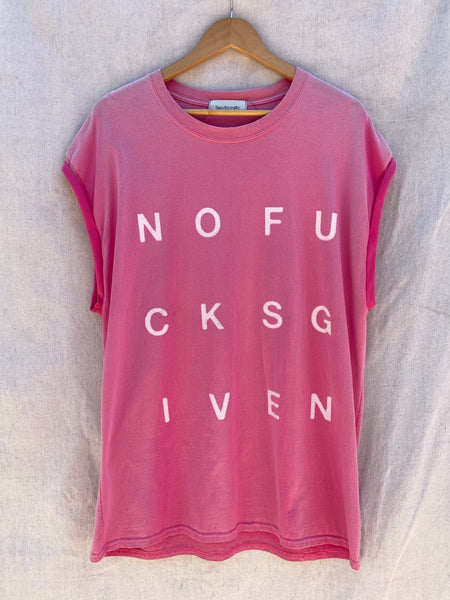 FRONT SHOT PINK MUSCLE TEE WITH NOFUCKSGIVEN WHITE LETTERS PRINTED ON IT.