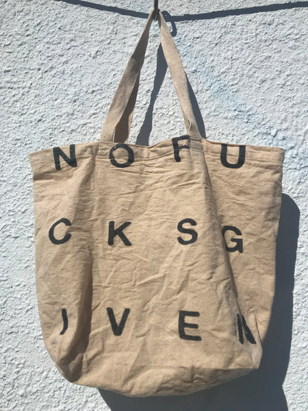 IMAGE OF TOTE BAG IN NATURAL MUSLIN COLOR. PRINT READS NOFUCKSGIVEN IN BLACK.