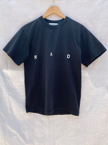 FRONT VIEW OF BLACK T-SHIRT WITH R A D EMBROIDERY ON IT.