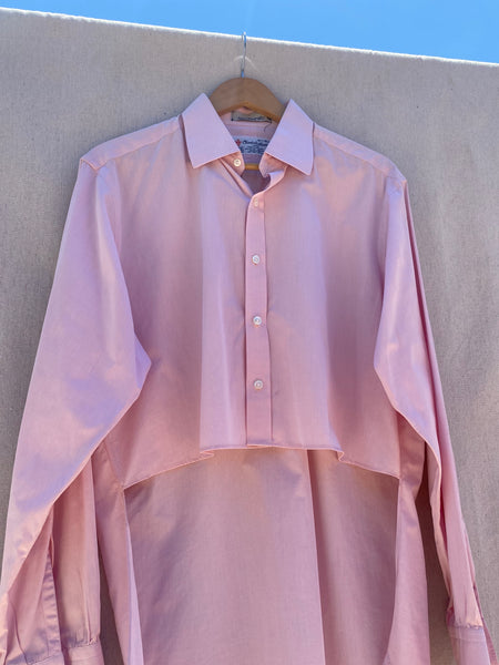 CLOSER VIEW OF FRONT HI-LO BUTTON DOWN LONG SLEEVES SHIRT IN PINK. DETAIL OF SHORTER FRONT HEM.