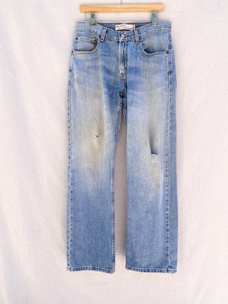 FRONT IMAGE OF DISTRESSED AND FADED BLUE JEANS.