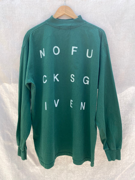 FULL BACK VIEW OF DARK GREEN LONG SLEEVES TEE. NOFUCKSGIVEN LETTERS IN WHITE IS PRINTED IN BLOCK LETTERS.
