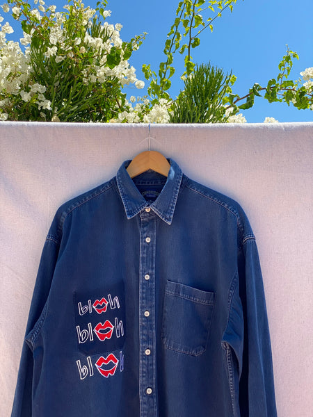 IMAGE OF BUTTON DOWN SHIRT WITH BLAH BLAH BLAH EMBROIDERY ON A WODDEN HANGER WITH GREEN FLOWERS AND BLUE SKY IN THE BACKGROUND.