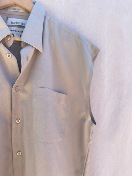 CLOSE UP VIEW OF SLEEVELESS BUTTON DOWN SHIRT, TOP LEFT CORNER, VIEW OF COLLAR, POCKET AND ARM HOLE.