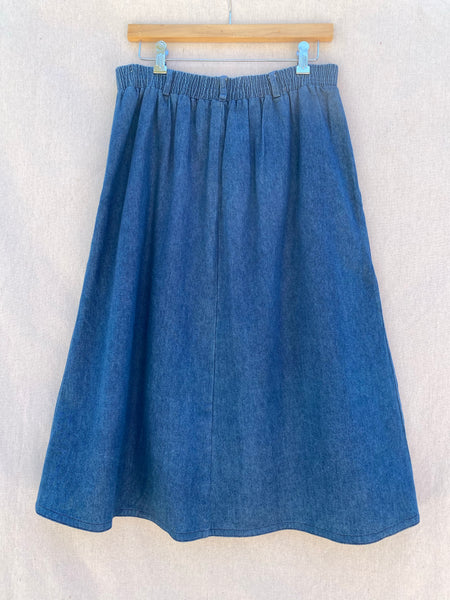 BACK VIEW OF  DENIM MIDI SKIRT WITH SHIRRED WAIST BAND.