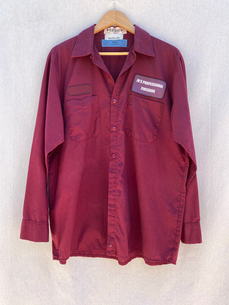 "FRONT VIEW OF MAROON UTILITY BUTTON DOWN SHIRT. 2 FRONT POCKETS. LEFT PATCH ABOVE POCKET READS ""JB'S PROFESSIONAL FINISHING"". LEFT PATCH IS BLANK."