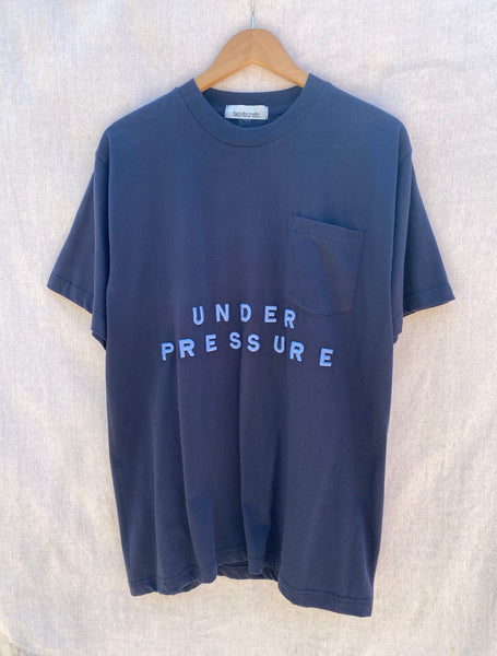 VIEW OF FRONT NAVY T-SHIRT WITH UNDER PRESSURE EMBROIDERED ON IT IN SKYBLUE THREAD.