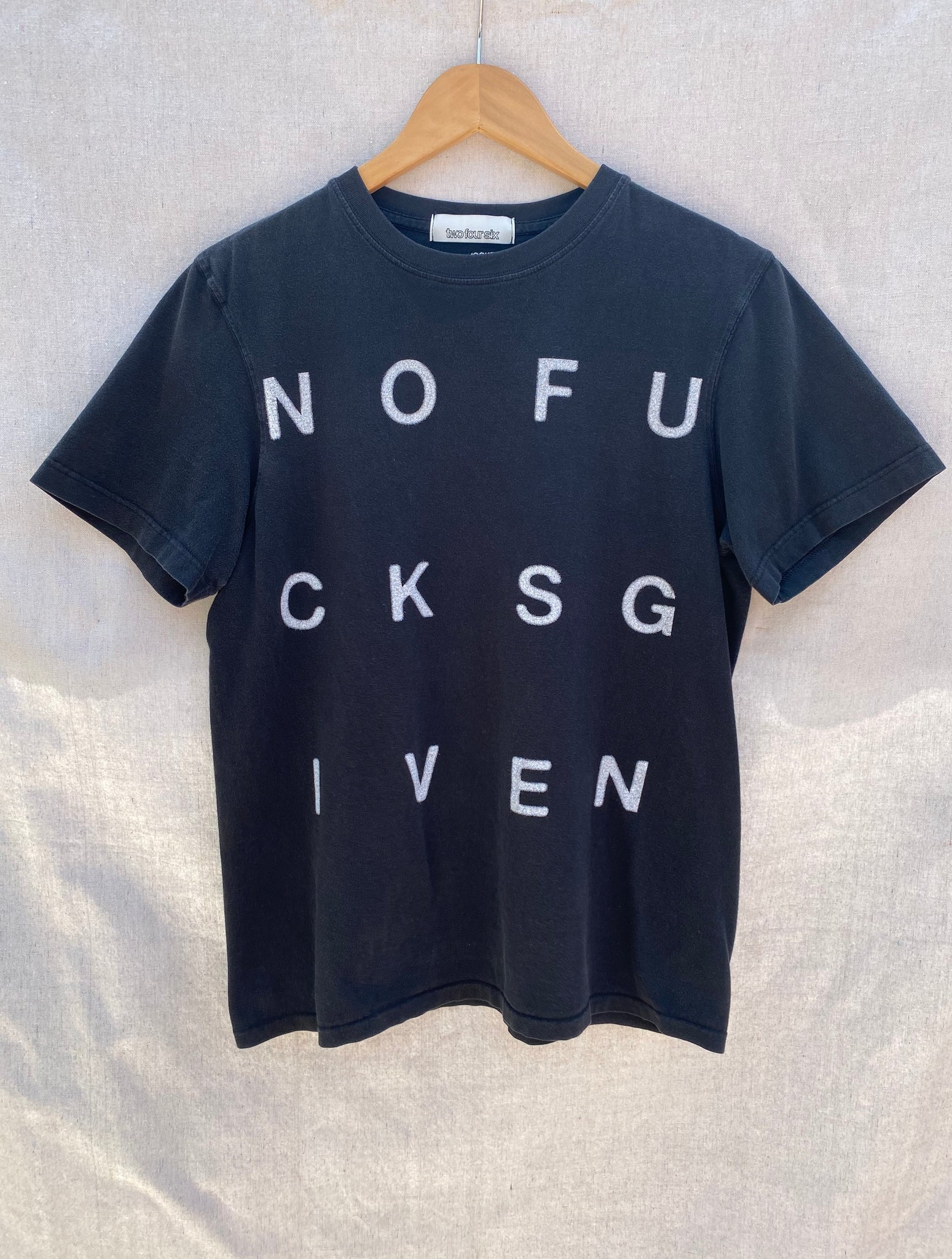 FONT VIEW FADED  BLACK T-SHIRT WITH WHITE NOFUCKSGIVEN PRINTED IN BLOCK LETTERS.