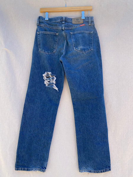 BACK IMAGE OF BLUE JEANS WITH HOLE AND FRAYING AT MID- LEFT LEG.