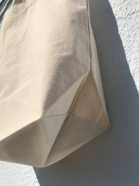 CLOSE UP VIEW OF BOTTOM CORNER OF TOTE BAG IN NATURAL MUSLIN COLOR.