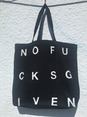 FRONT VIEW OF BLACK TOTE BAG WITH NOFUCKSGIVEN PRINT IN WHITE.