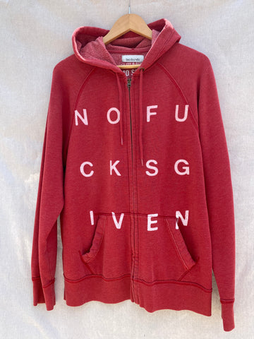 FRONT VIEW OF FADED RED ZIP UP HOODIE WITH NOFUCKSGIVEN PRINT ON IT. HOODIE HAS SIDE POCKETS.