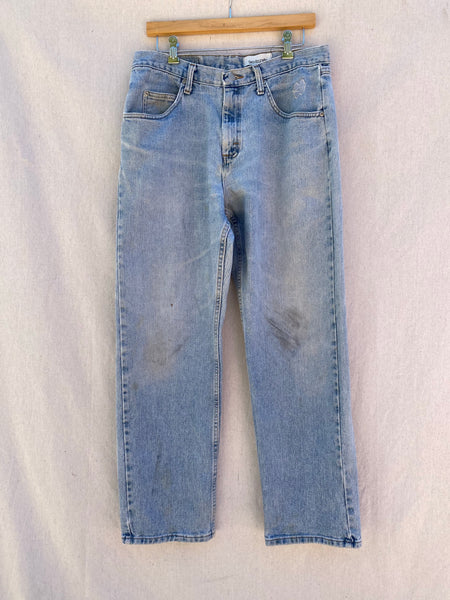 FRONT IMAGE OF FADED AND STAINED BLUE JEANS.