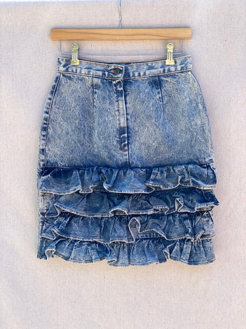 DENIM SHORT SKIRT WITH 4 LAYERS OF RUFFLES AT HEM. BUTTON WAIST BAND AND HIDDEN ZIP CLOSURE.