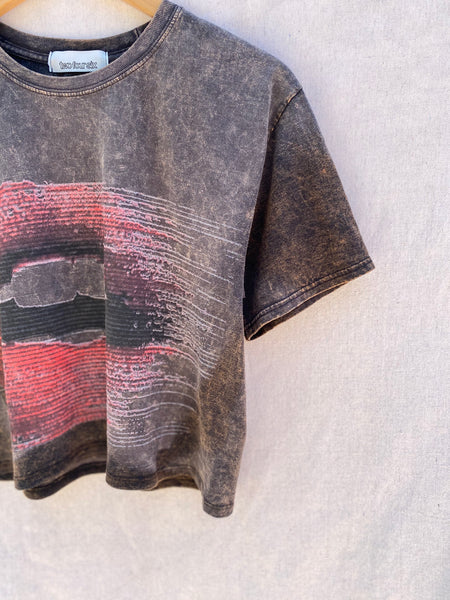 CLOSE UP VIEW OF FRONT LEFT NECK AND SLEEVE. HALF OF LIP PRINT IS VISIBLE.